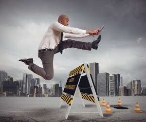 Businessman running over hurdle. Technology blog - Voy Tech